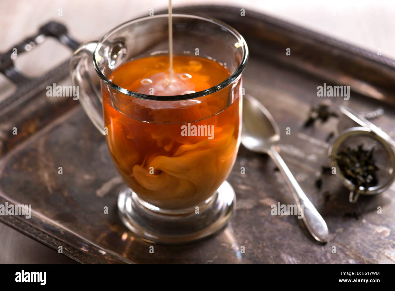 A glass of tea with milk pouring in and swirling. Antique, rustic styling with light background. Stock Photo