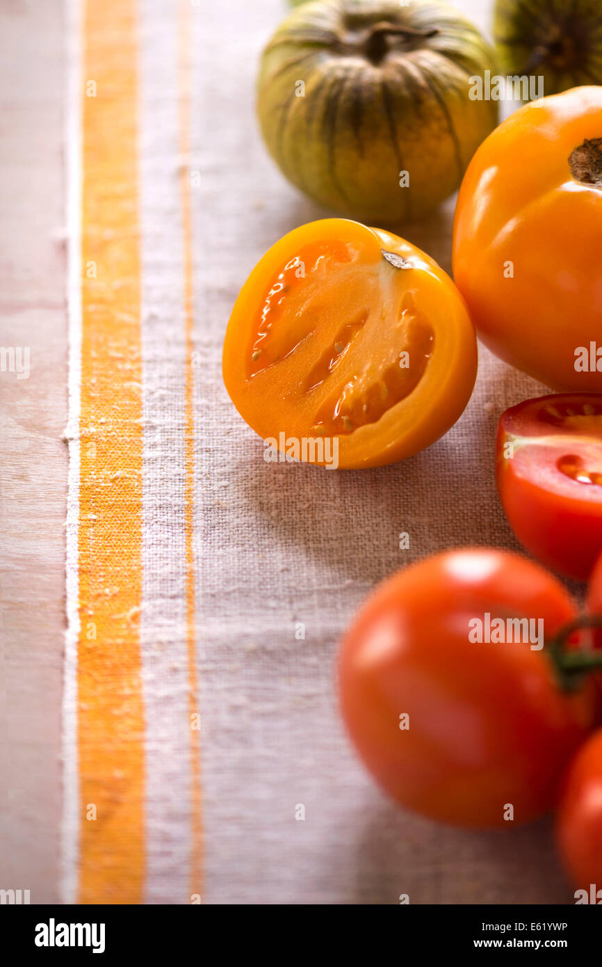 Variety of tomatoes whole and cut on rustic linen. Light, summery feel. - Stock Image
