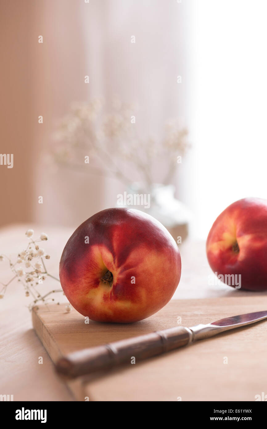 White nectarines on cutting board with white flowers. Light, bright, natural background. - Stock Image