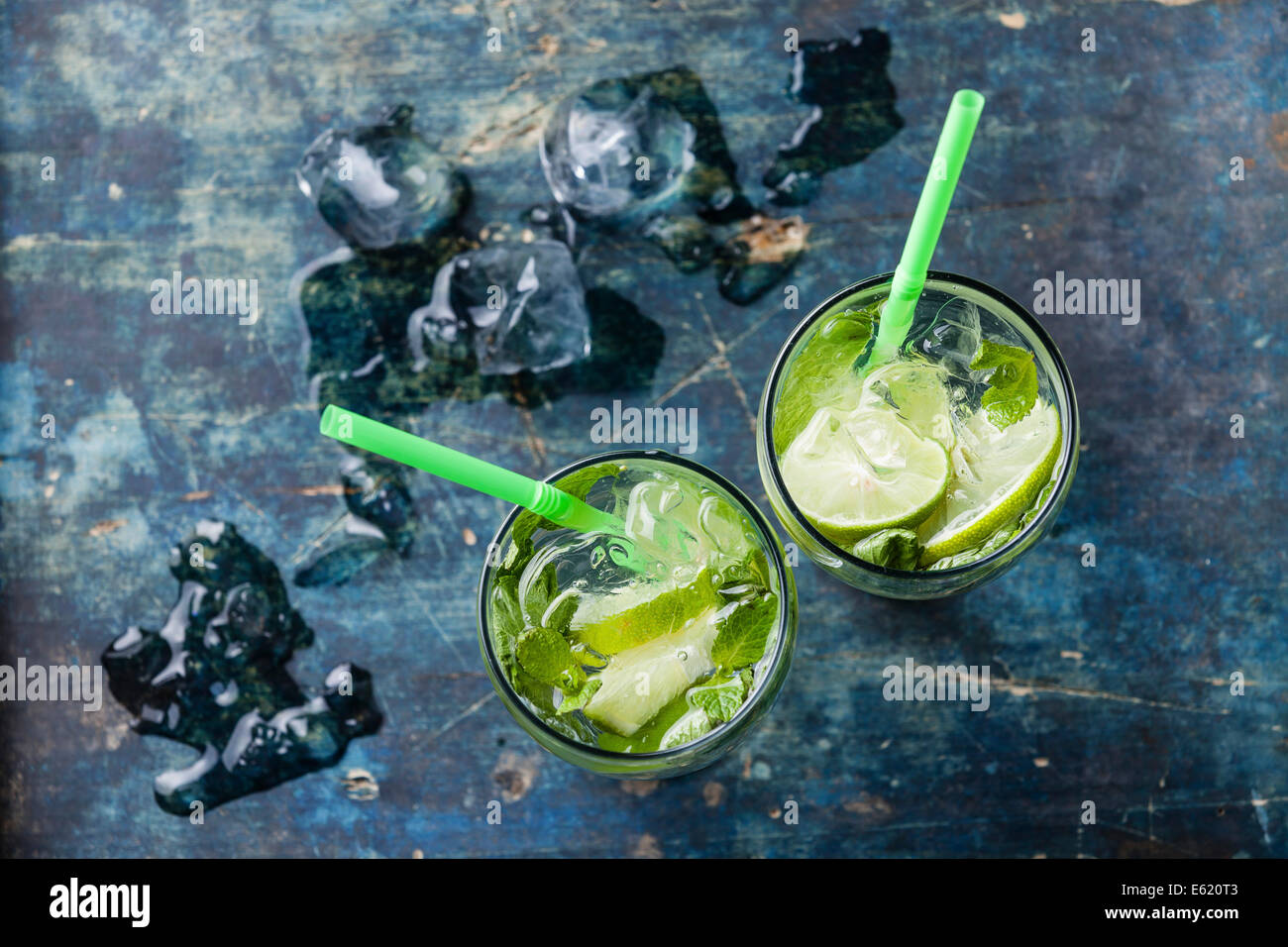 Glass of iced Mojito cocktail with mint on blue background - Stock Image
