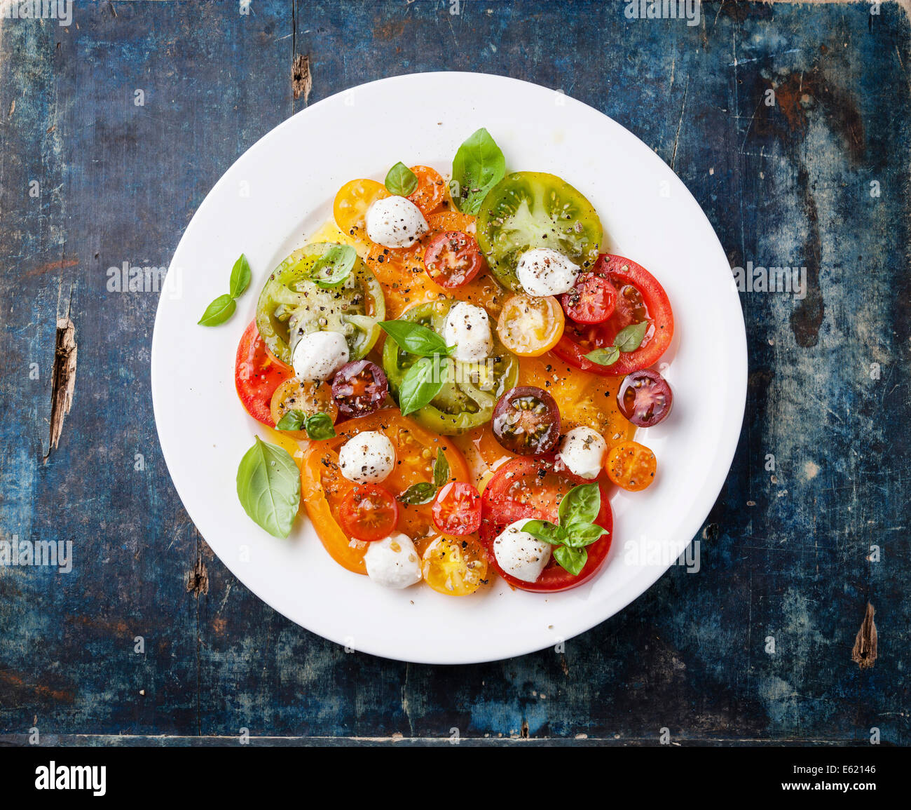 Colorful tomatoes salad with mozarella on blue wooden background - Stock Image
