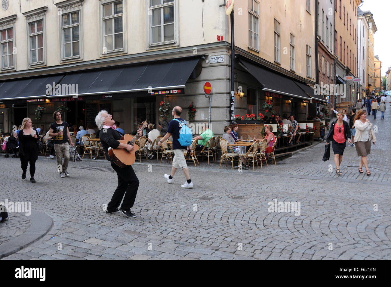 Street life in old Stockholm with sidewalk restaurants, coffee shops, pedestrians and musicians along cobblestone - Stock Image