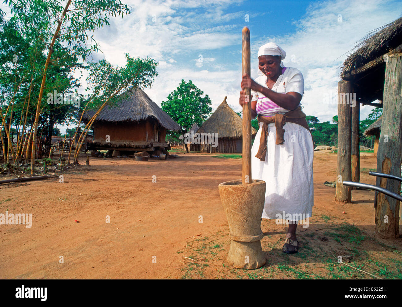 Woman pounding maize for cornbread in Zimbabwe village - Stock Image