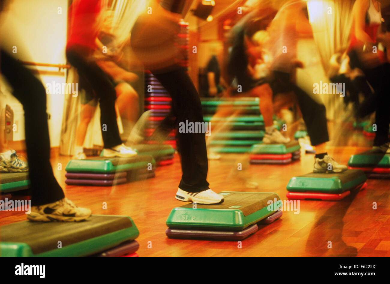 Legs and shoes in motion during stepping exercise class - Stock Image