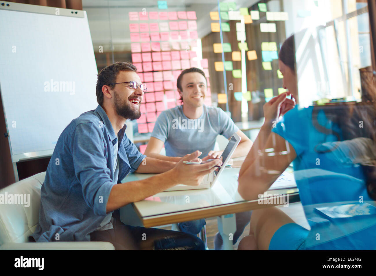 Young business partners sharing ideas and planning work at meeting in office - Stock Image
