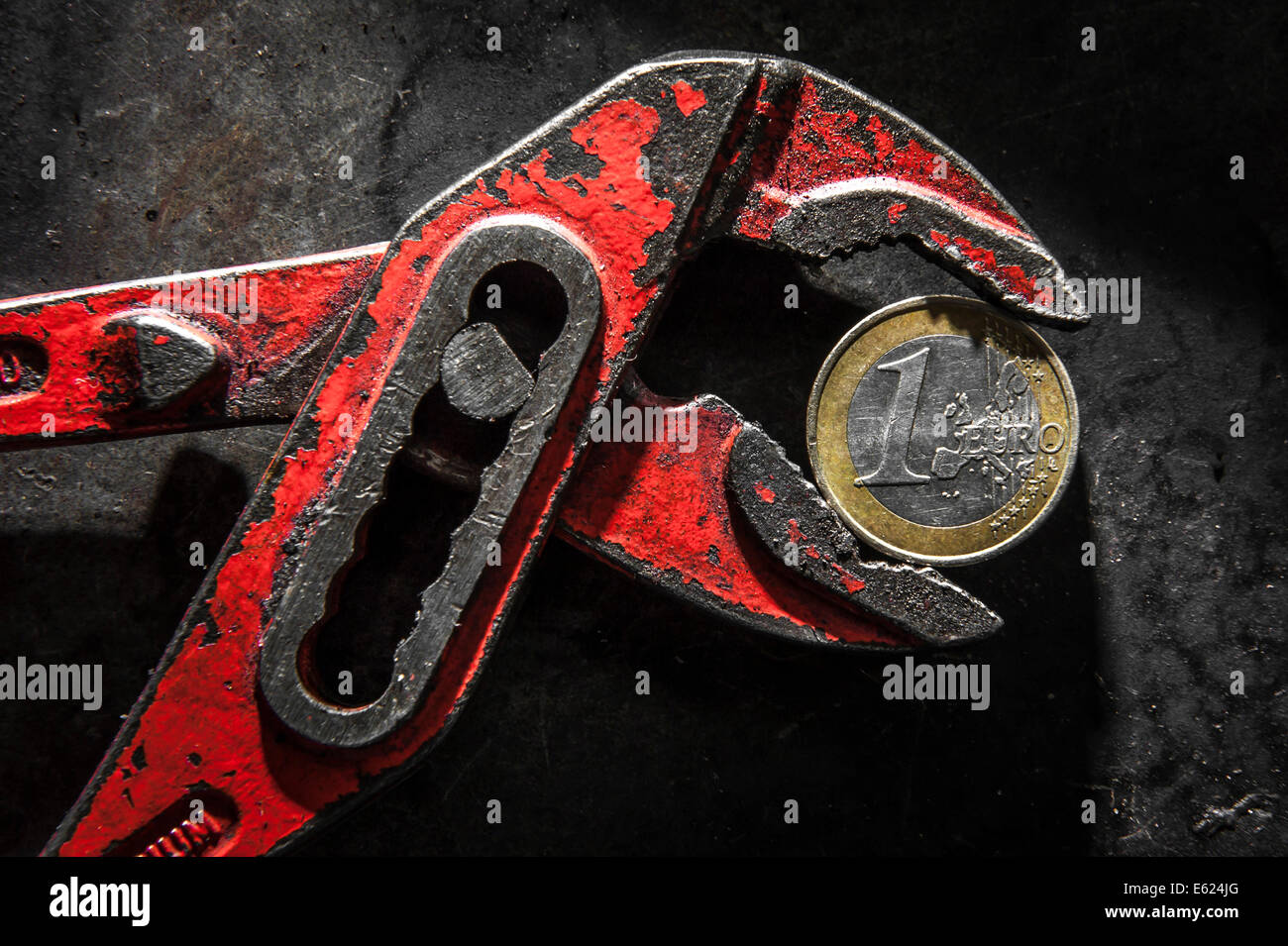A Greek euro coin under pressure in a monkey wrench - Stock Image