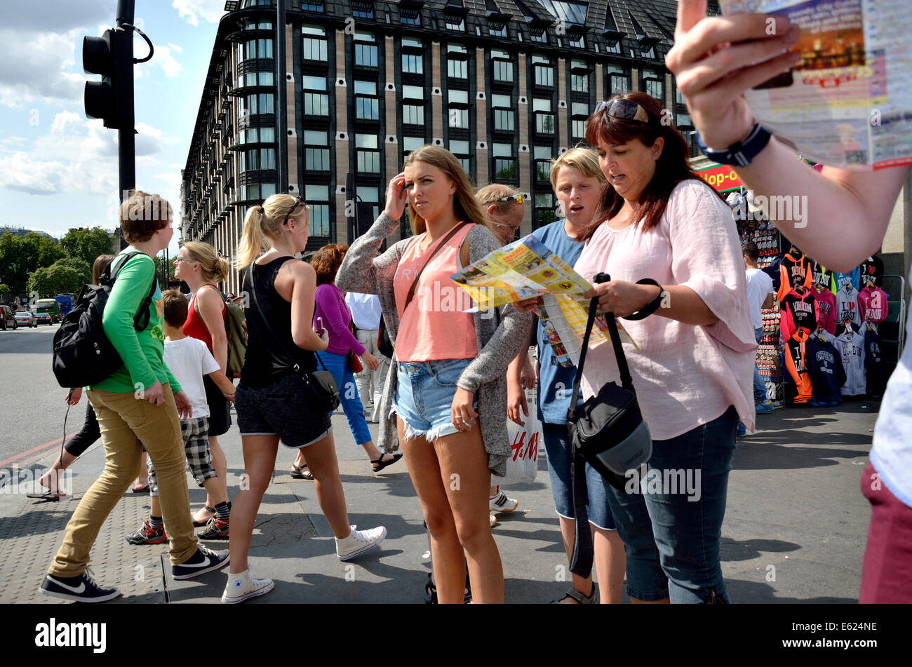 London, England, UK. Family looking at a map on Westminster Bridge - Portcullis House behind - Stock Image