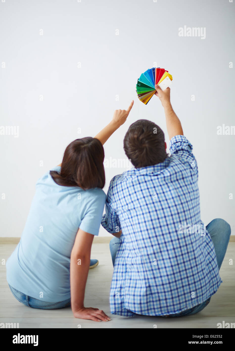 Backs of man and woman sitting on the floor of new house and choosing color of walls - Stock Image