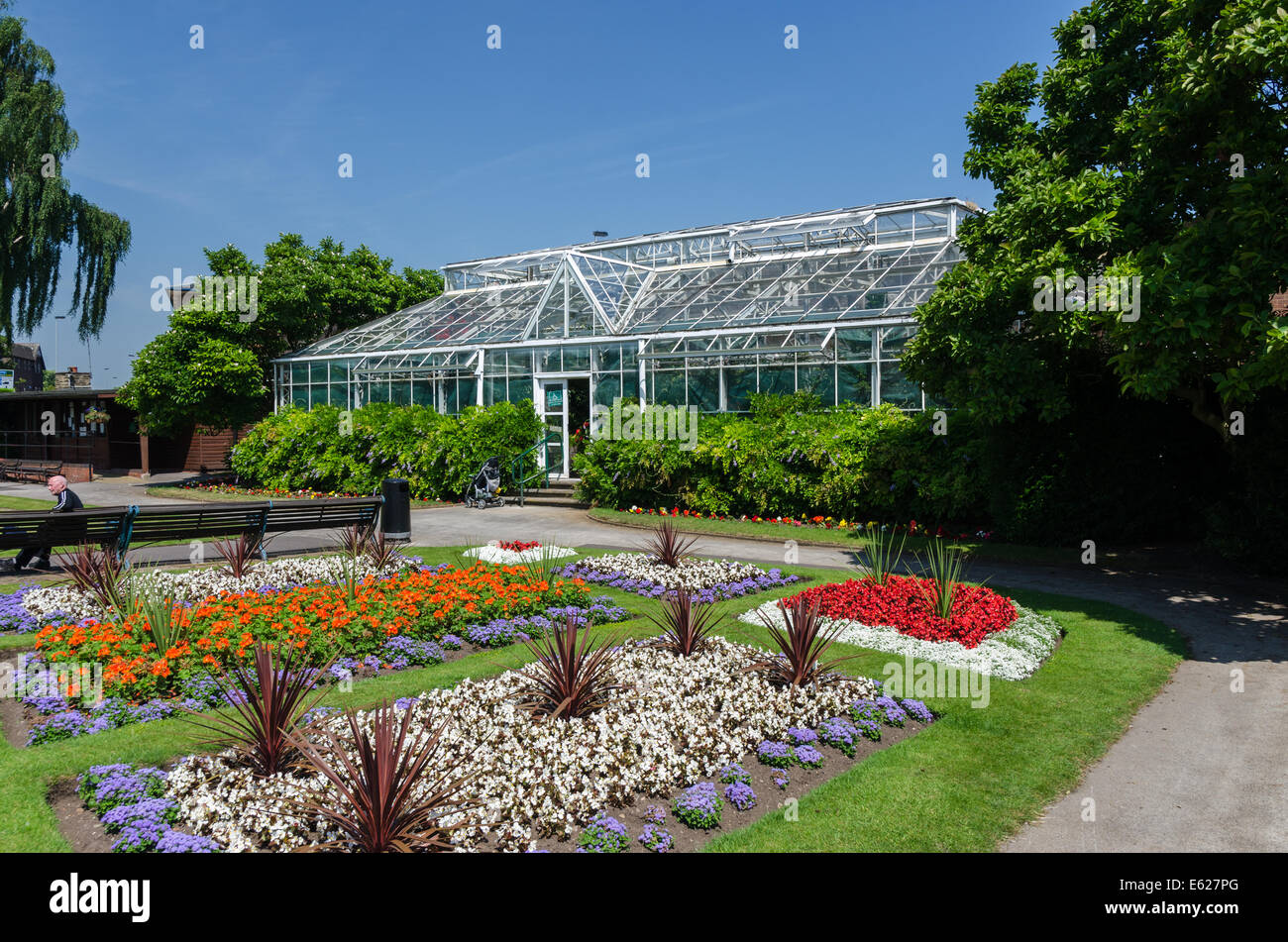 Glasshouses and colourful flowerbeds in Victoria Park in Stafford - Stock Image