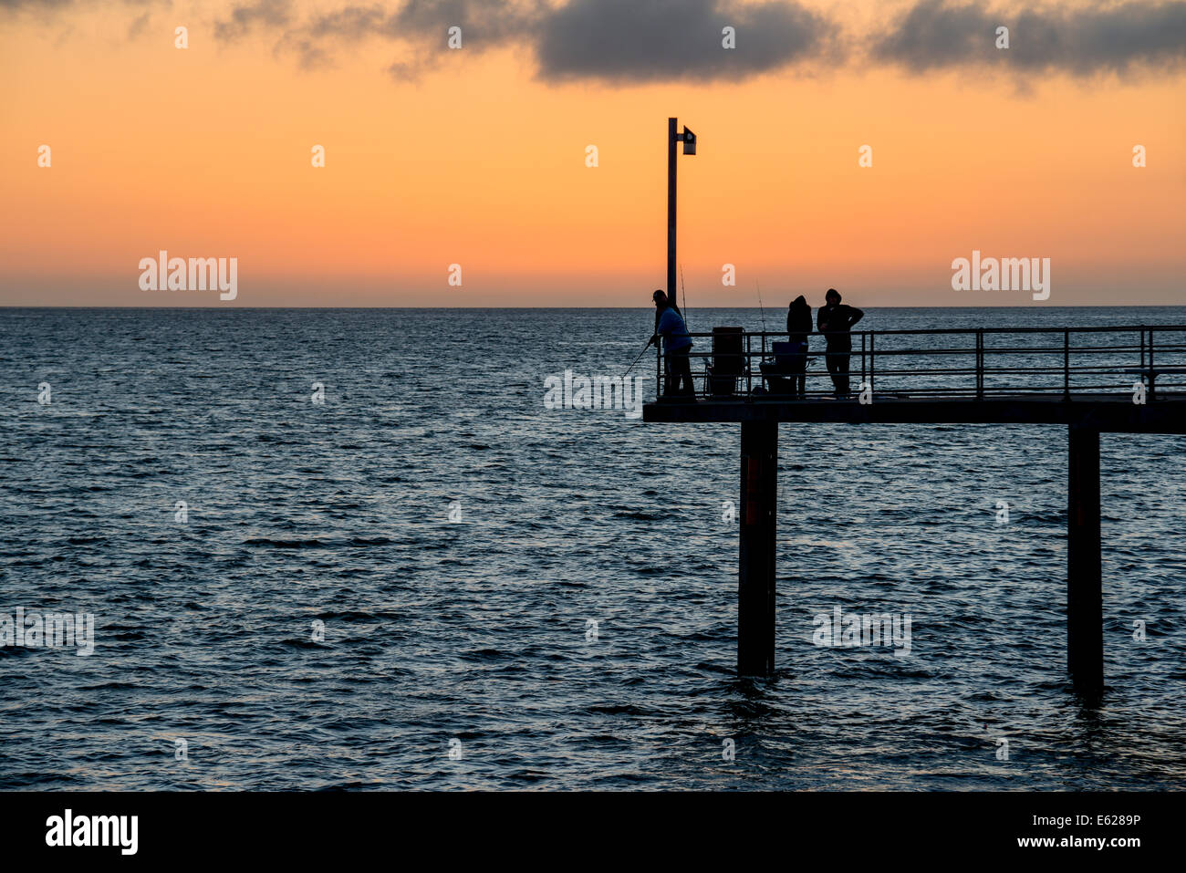 Fishermen on the pier are silhouetted against the sunset at Adelaide's Brighton beach, Australia - Stock Image
