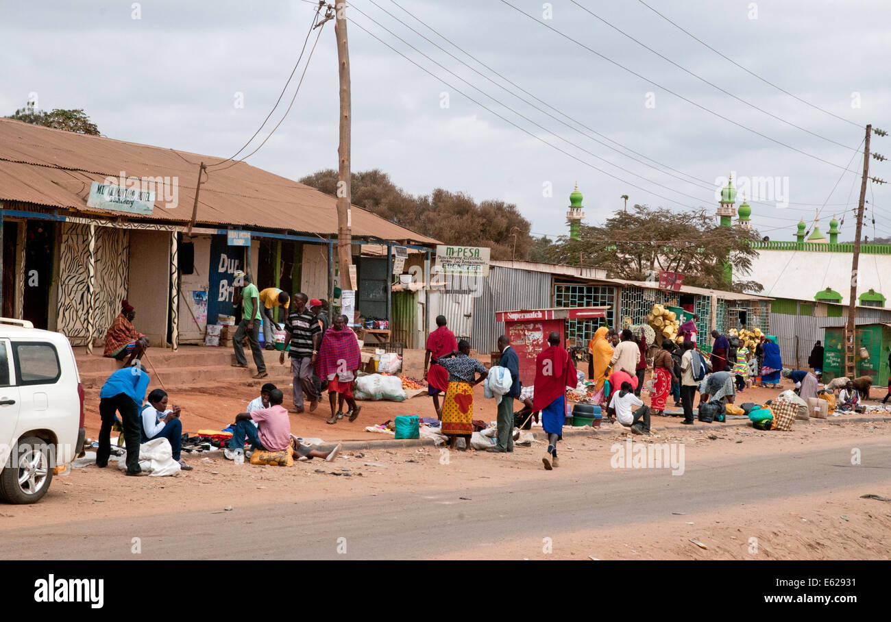 People at third world corrugated iron shacks and roadside shops duka hotel on Namanga Nairobi road Kenya East Africa - Stock Image