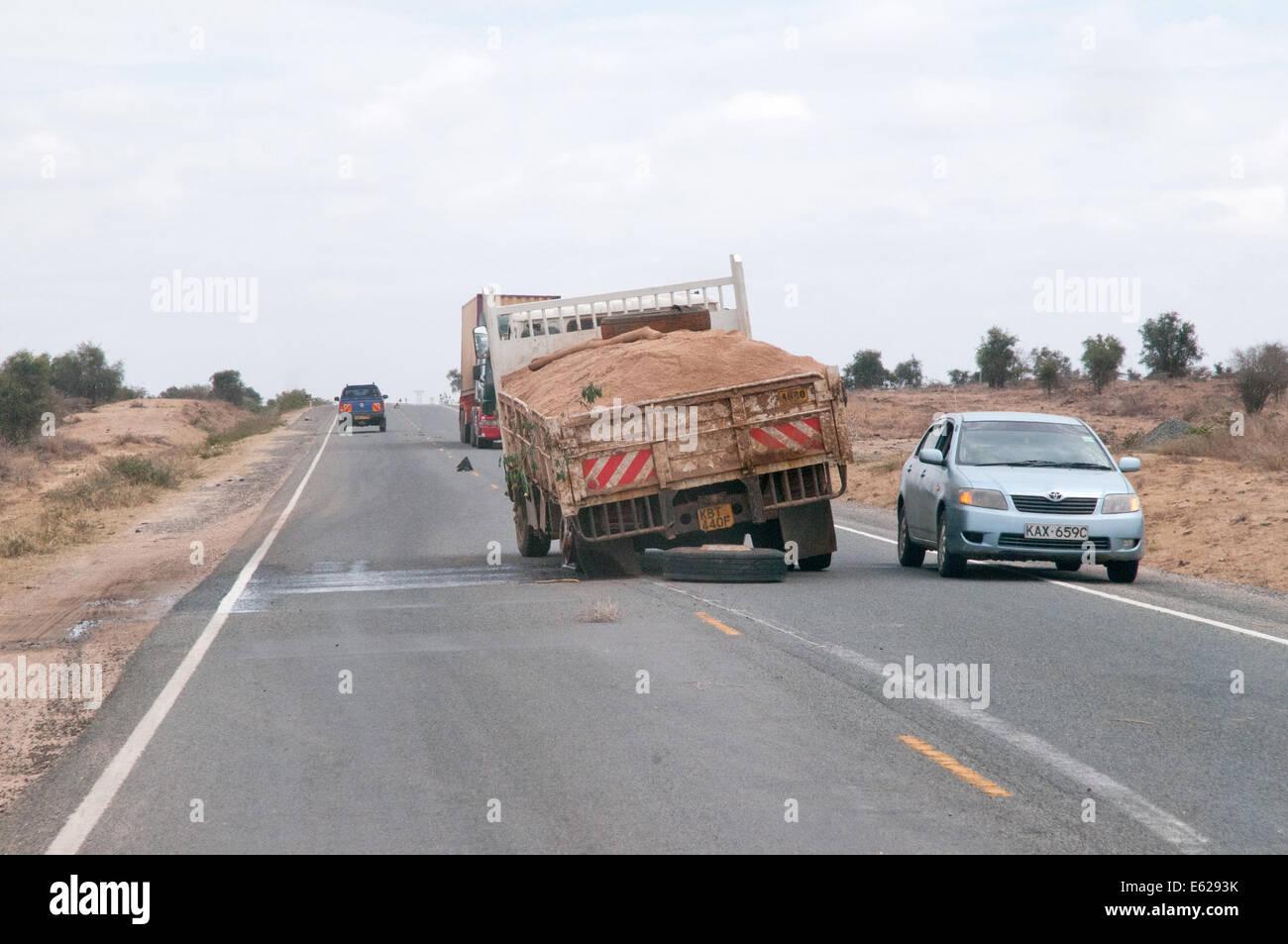 Traffic passing broken down truck lorry with broken rear spring on Namanga Nairobi Road Kenya East Africa - Stock Image