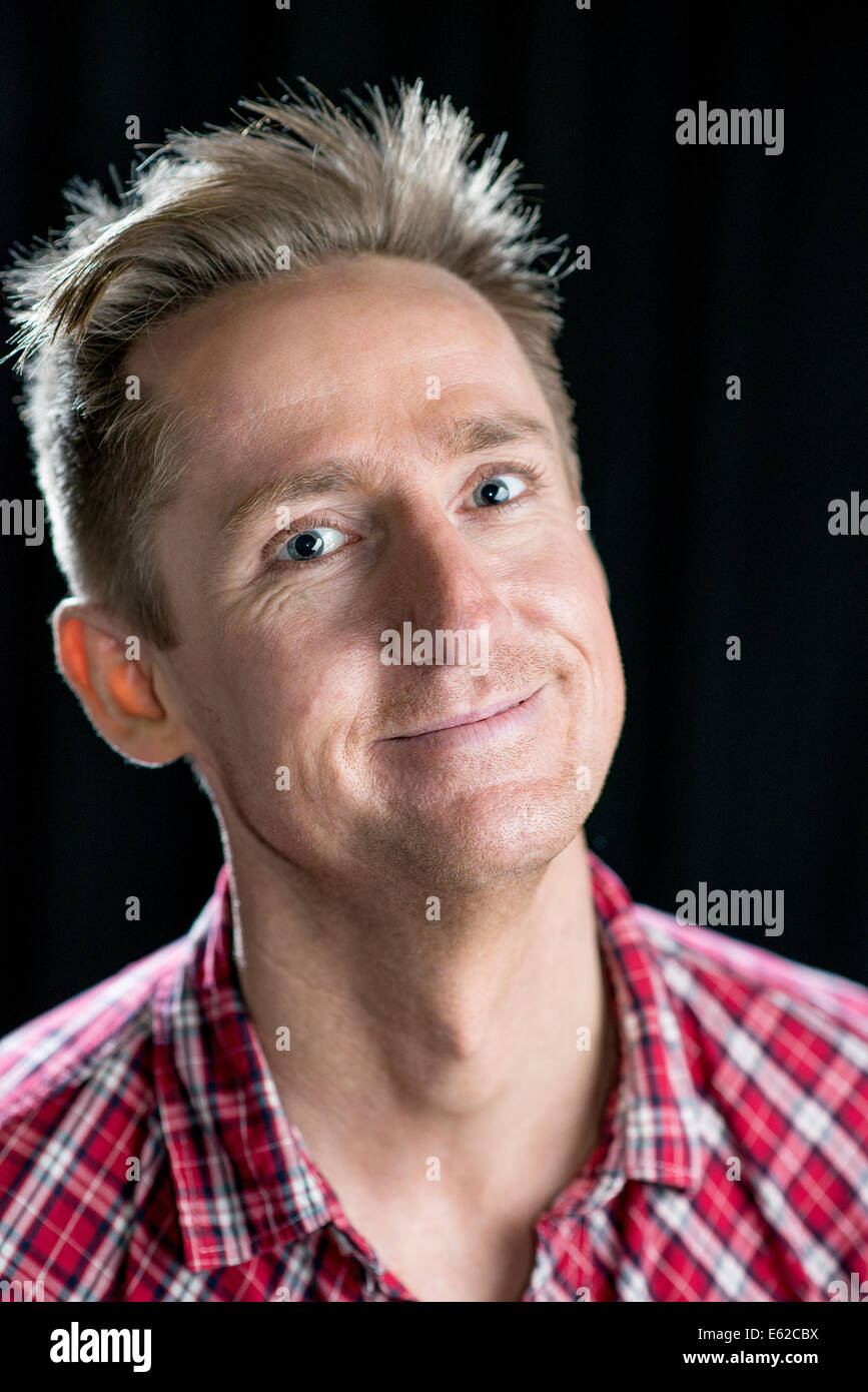 Headshots on black of a good looking man in his thirties with various facial expressions. - Stock Image