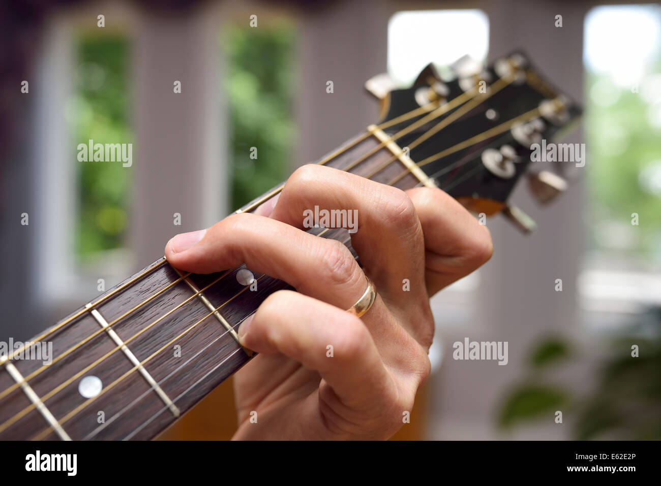 Close up of a man with hand on acoustic guitar showing chord fingering on the fretboard - Stock Image