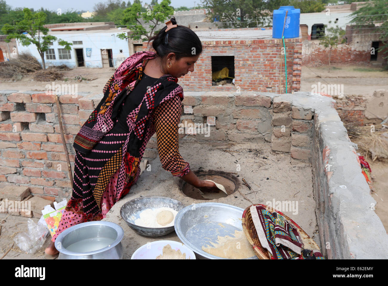 Woman in traditional dress baking roti bread (known as chapati) in a clay oven. Khushpur Village, Punjab Province, - Stock Image