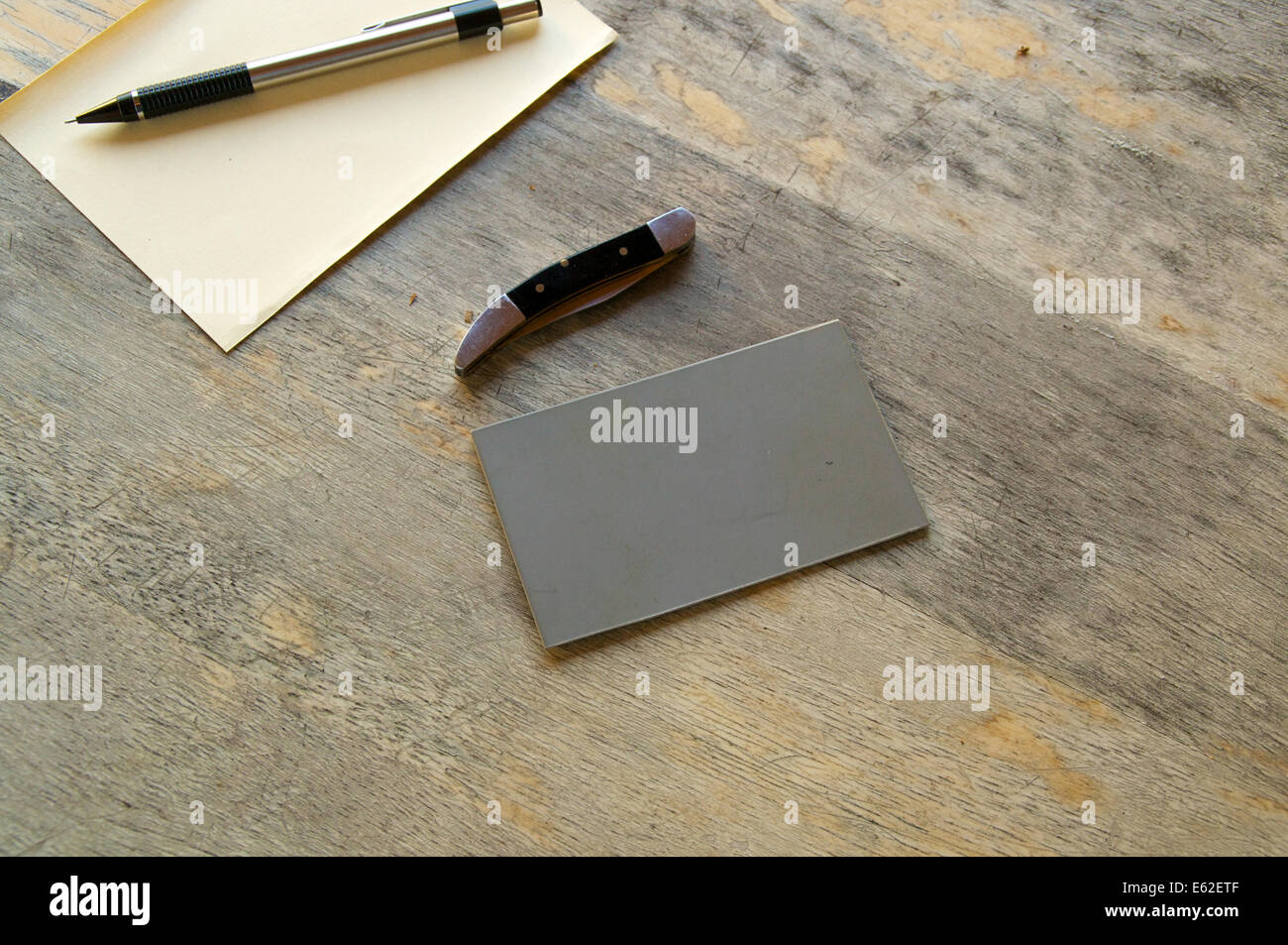 A pencil, paper, knife and grey card are seen on an old wooden table. Stock Photo