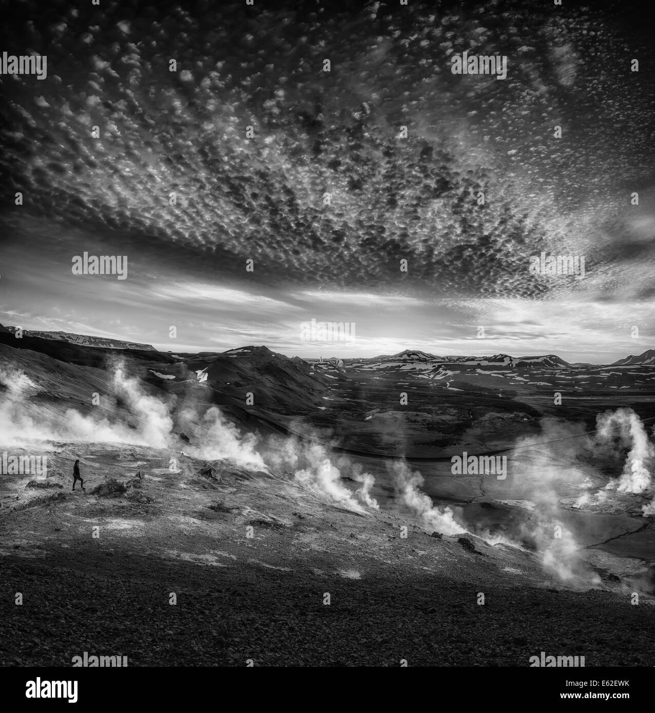 Woman standing by Geothermal hot springs, mud pots and fumaroles, Namaskard close to Lake Myvatn, Northern, Iceland - Stock Image