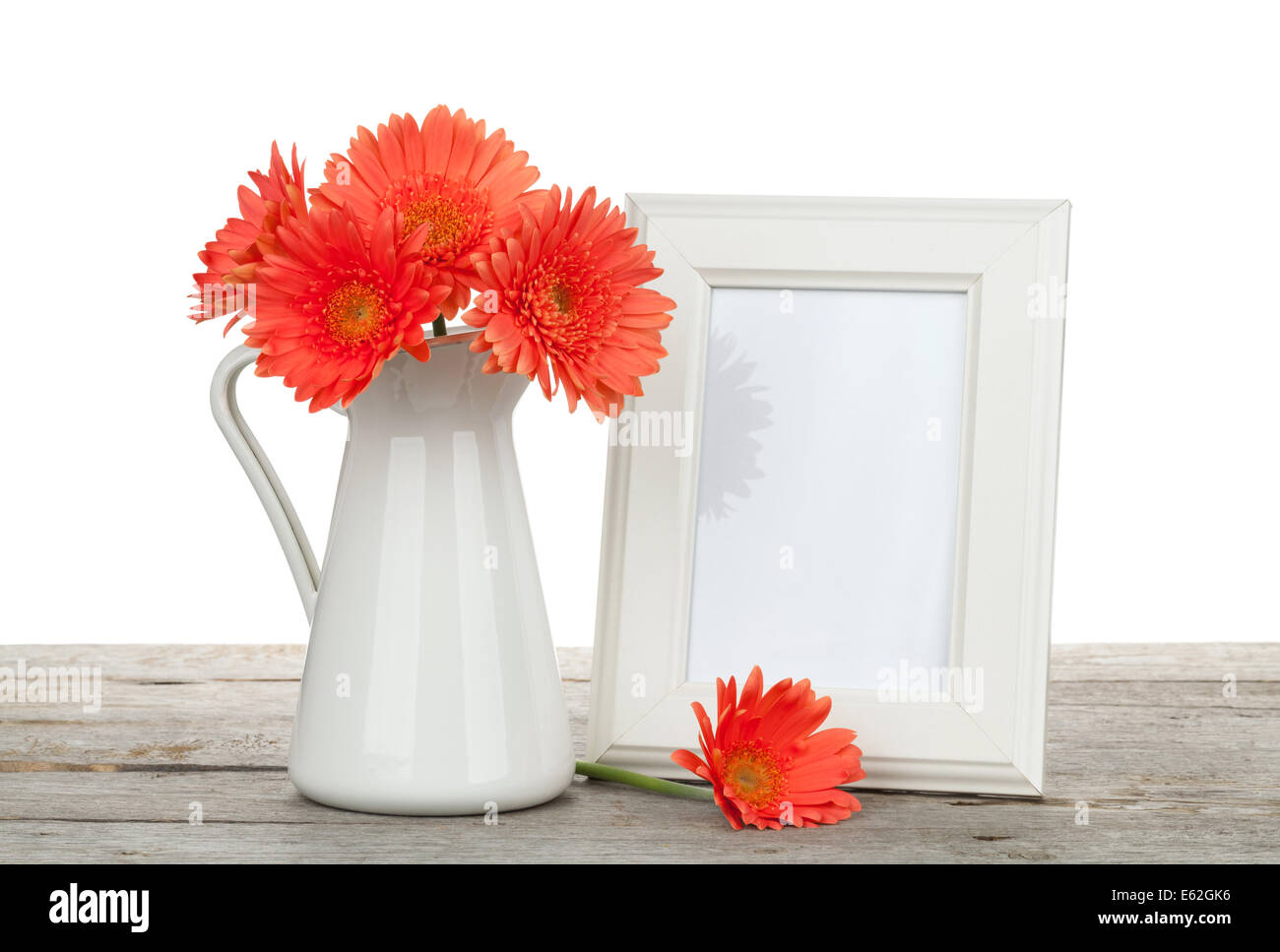 Orange Gerbera Flowers And Photo Frame On Wooden Table On White