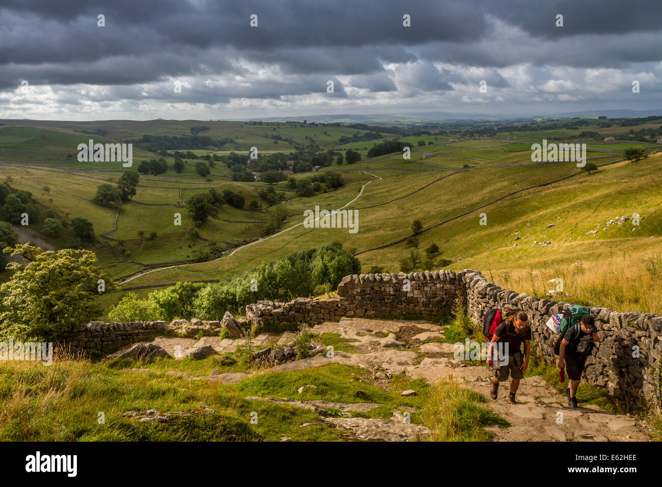 Backpackers ascending the beautiful path by Malham Cove, Yorkshire Dales - Stock Image
