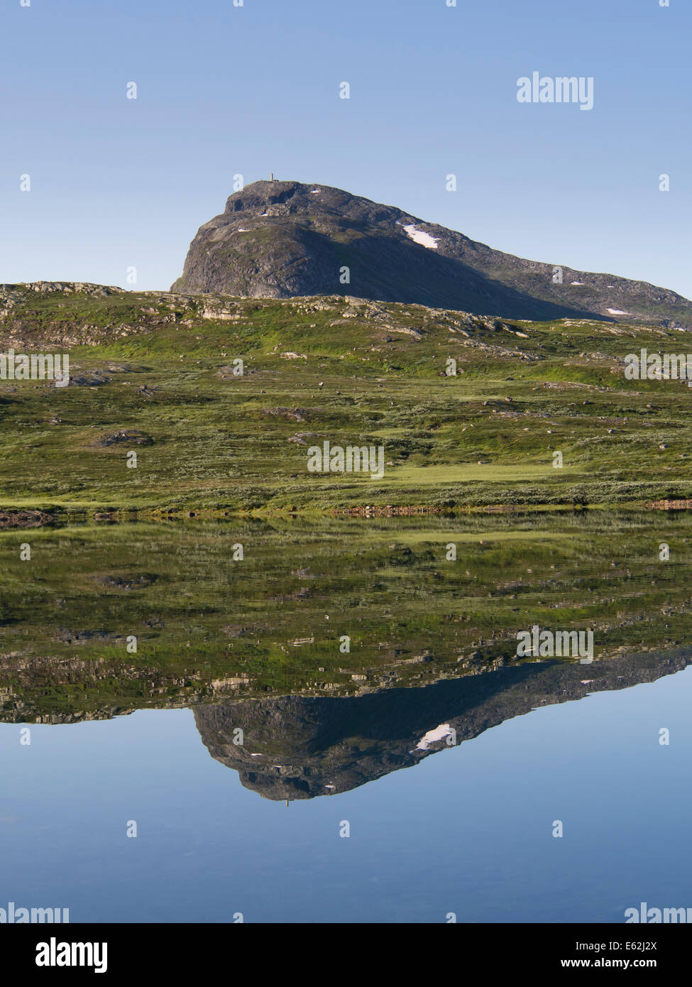 Hills and mountaintop Bitihorn in Jotunheimen Norway reflected in the clear waters of lake Bygdin one early summer - Stock Image