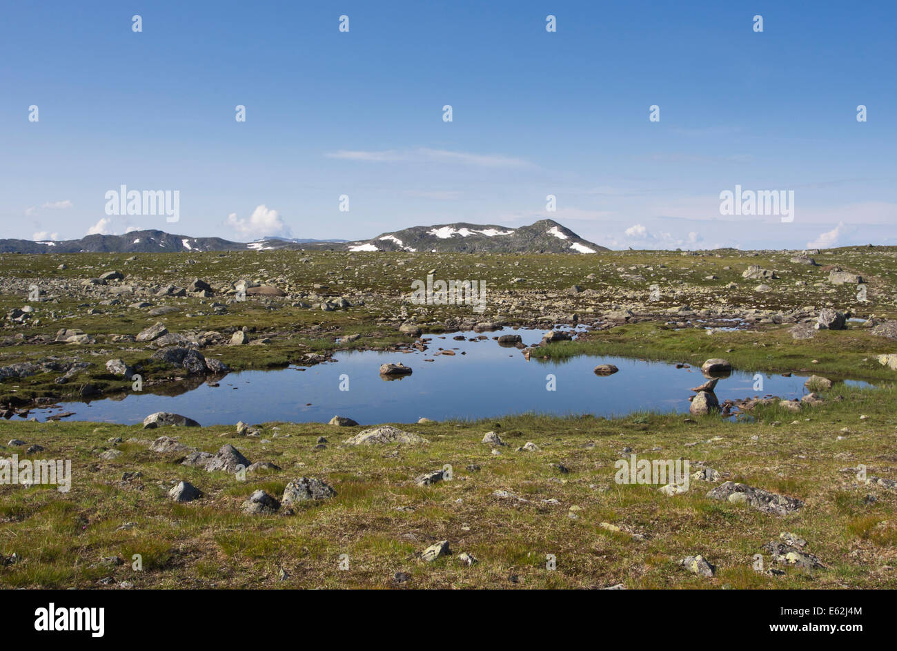 Valdresflya in Jotunheimen Norway, barren but inviting in the summer sun, small lake reflecting the blue sky - Stock Image
