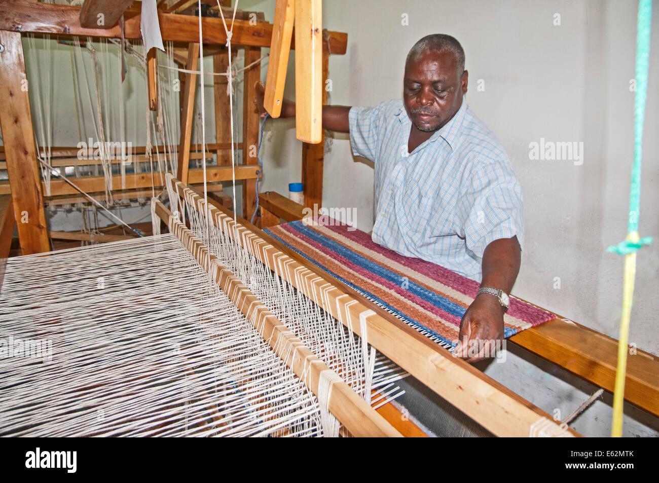 Black African man weaving a woollen rug on loom at Elmentieta Weavers on Lake Road Naivasha Kenya Africa  LOOM WEAVE - Stock Image