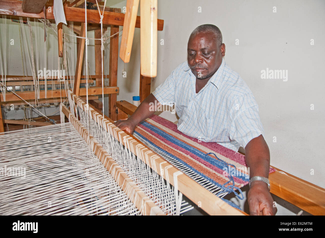 Black African man weaving a woollen rug on loom at Elmentieta Weavers on Lake Road Naivasha Kenya Africa  LOOM WEAVE - Stock Image