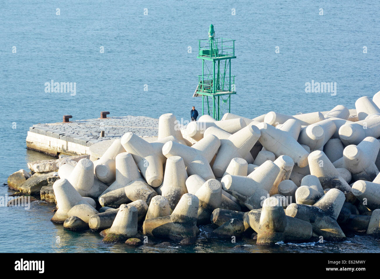 Man standing beside Dolosse precast concrete blocks in breakwater to protect  green channel marker on the harbour - Stock Image