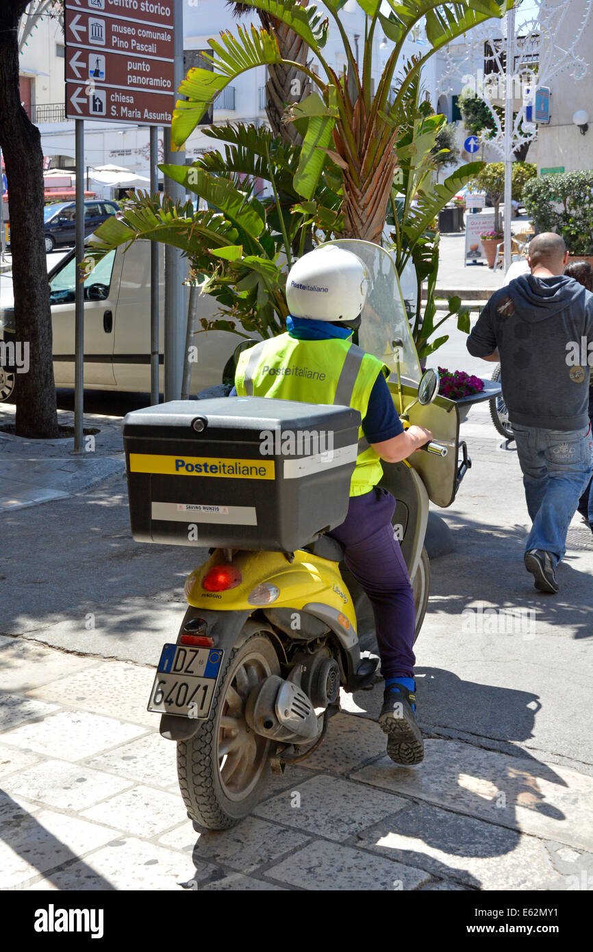 Italian postman on motor bike with large box at rear making deliveries in Polignano a Mare town centre - Stock Image