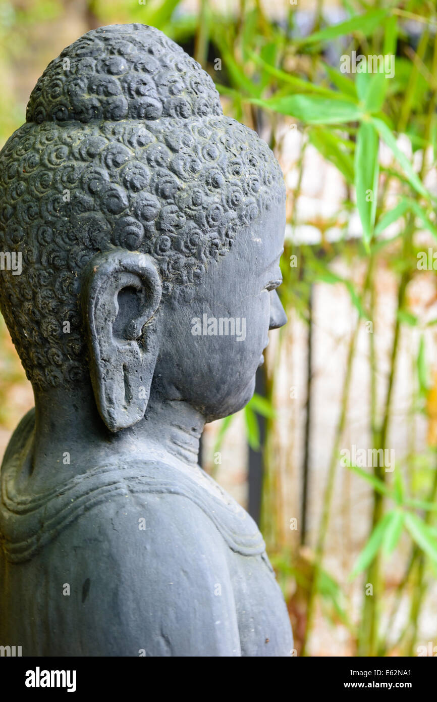 close-up of statue of buddha in zen garden with bamboo Stock Photo