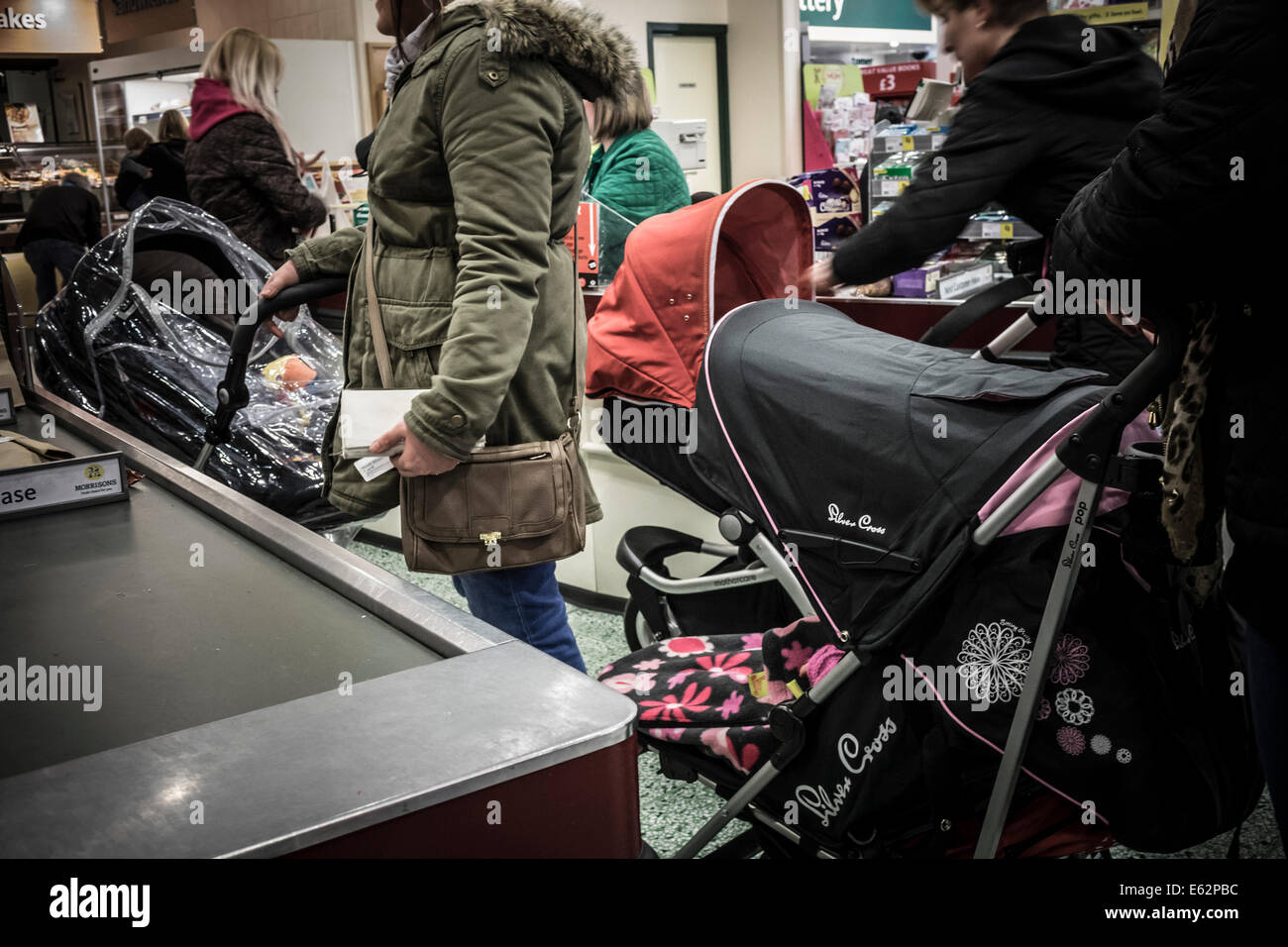 Supermarket stroller traffic jam at the checkout as young mums shop together - Stock Image
