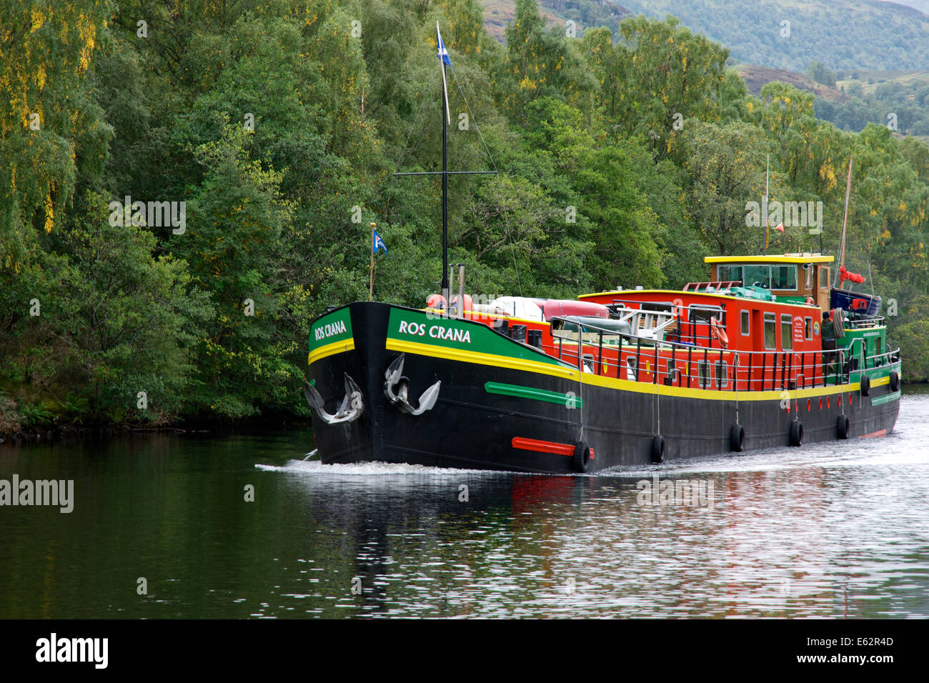 A hotel boat moves along the Caledonian canal to meet up with its customers - Stock Image