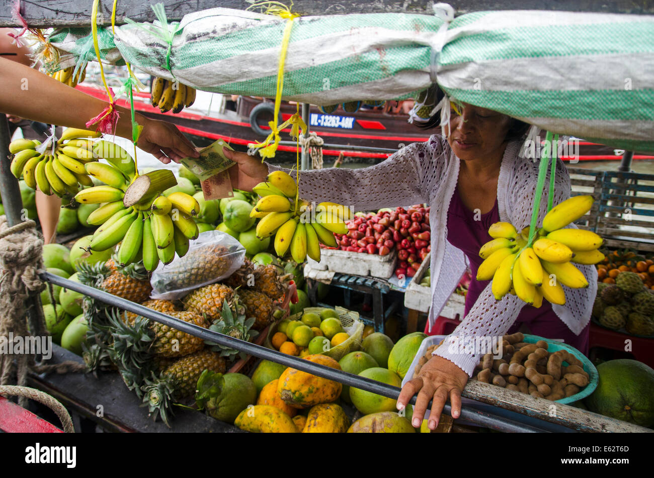 Woman selling fruit & vegetables on boat, Cai Be floating market, Vietnam - Stock Image