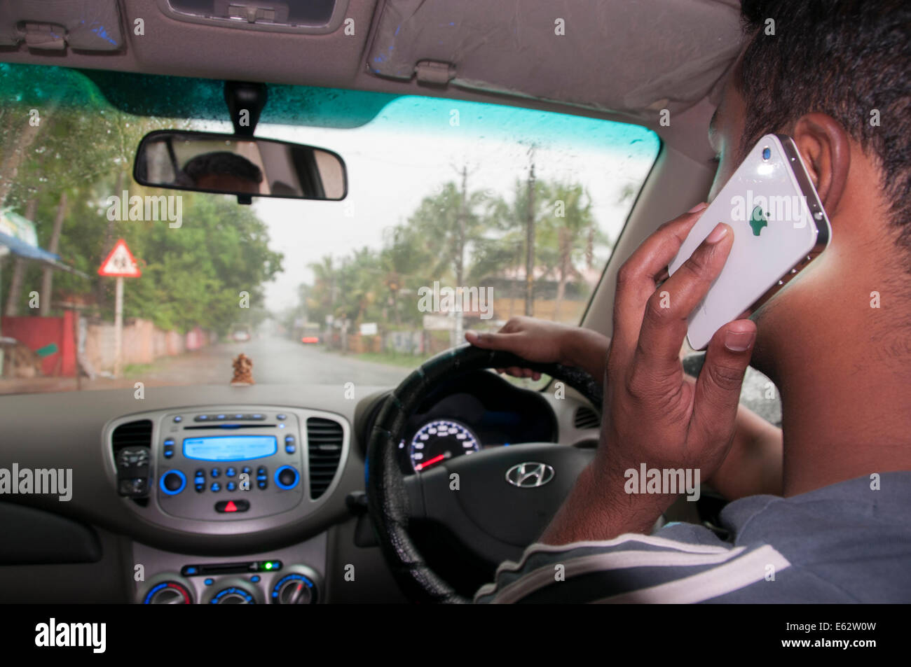Driving and talking on mobile cell phone - Stock Image