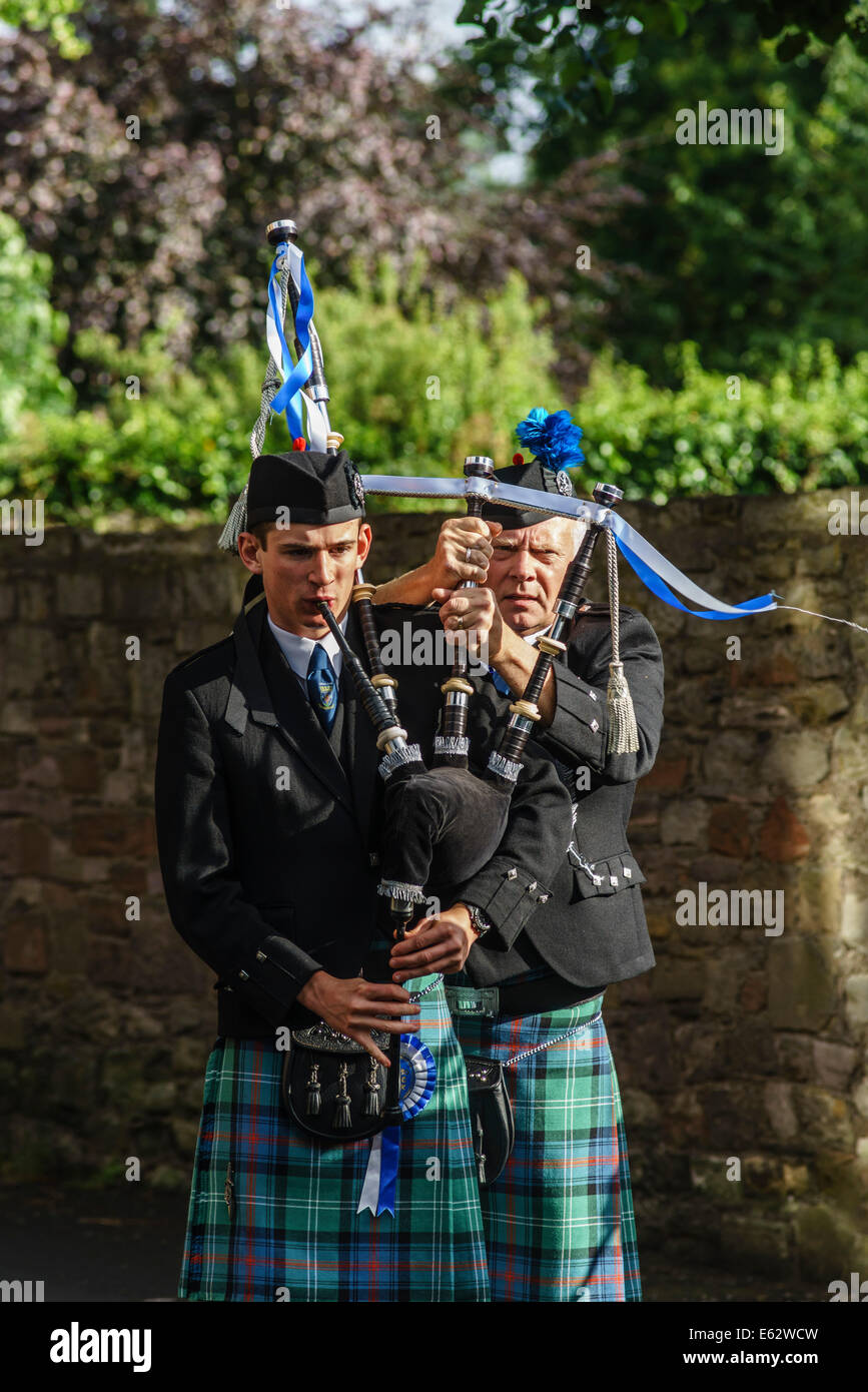 Kelso, Scottish Borders - helojng a piper get his drones in tune before a band march. - Stock Image