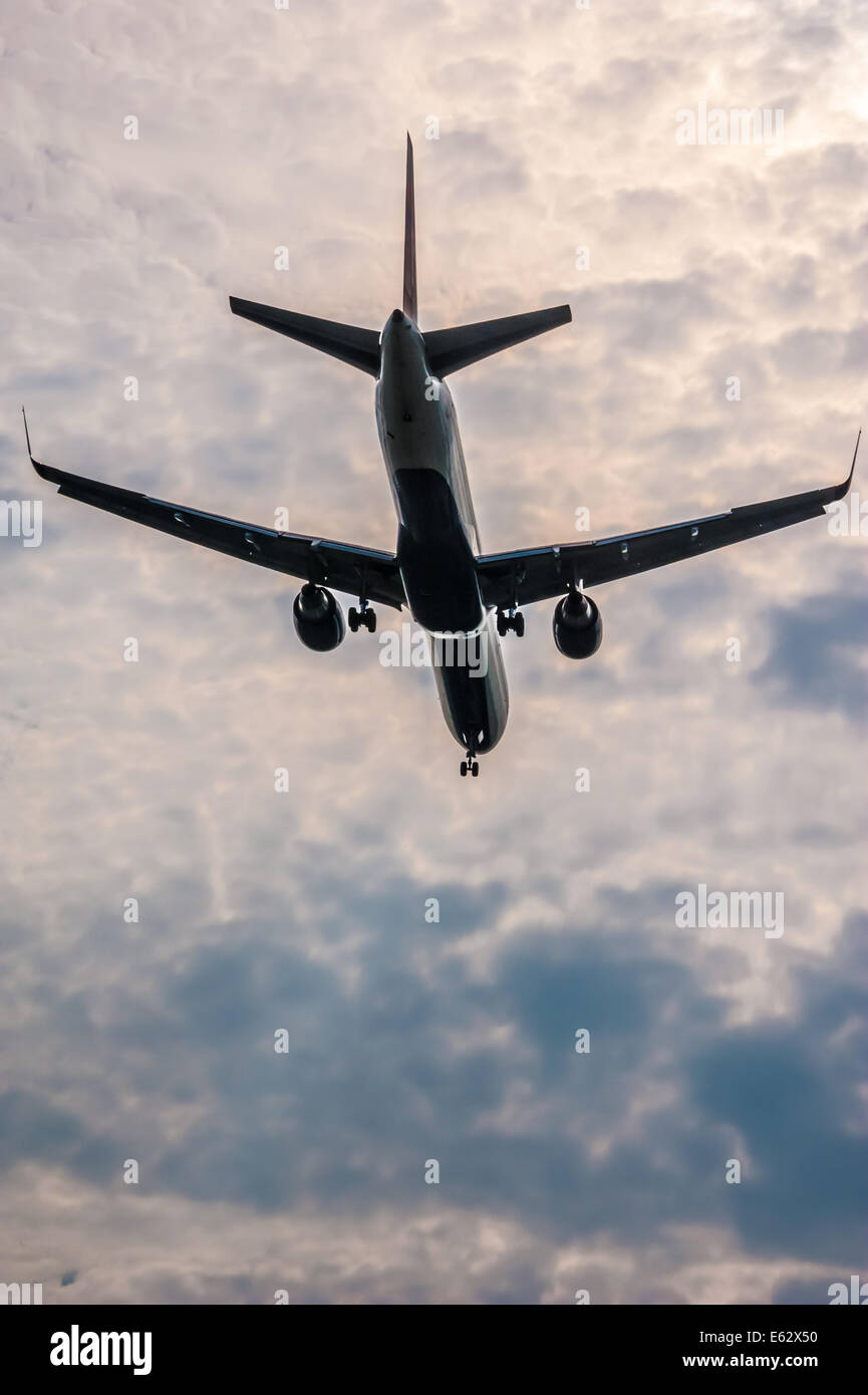 Passenger airline jet descending on approach for landing against a dramatic backdrop of sunlit clouds. Atlanta, - Stock Image