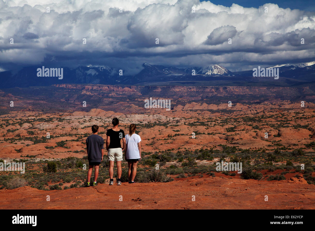 Tourists looking dark clouds over La Sal Mountains, from Arches National Park, near Moab, Utah, USA - Stock Image