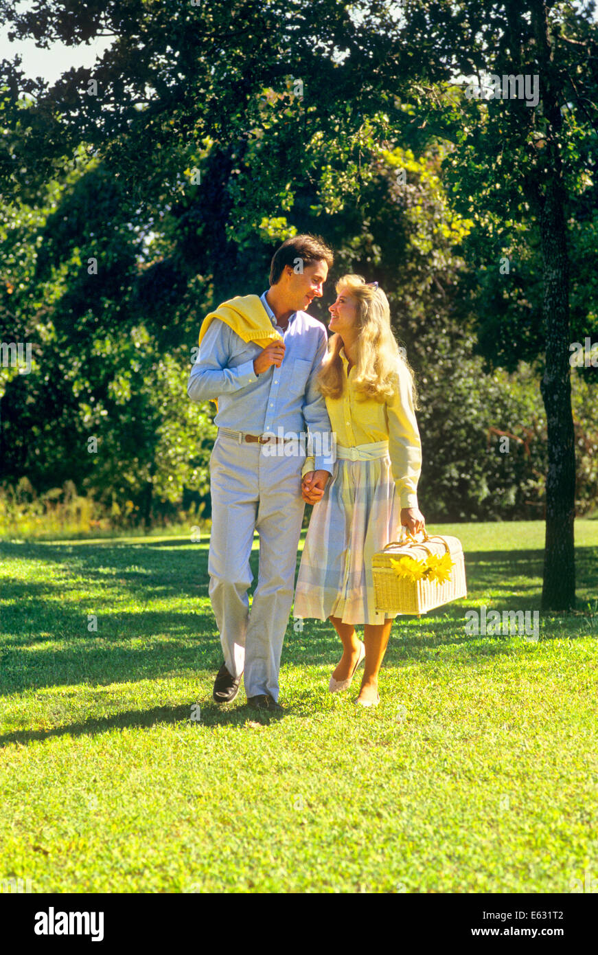 1980s YOUNG COUPLE WALKING OUTDOORS CARRYING PICNIC BASKET - Stock Image