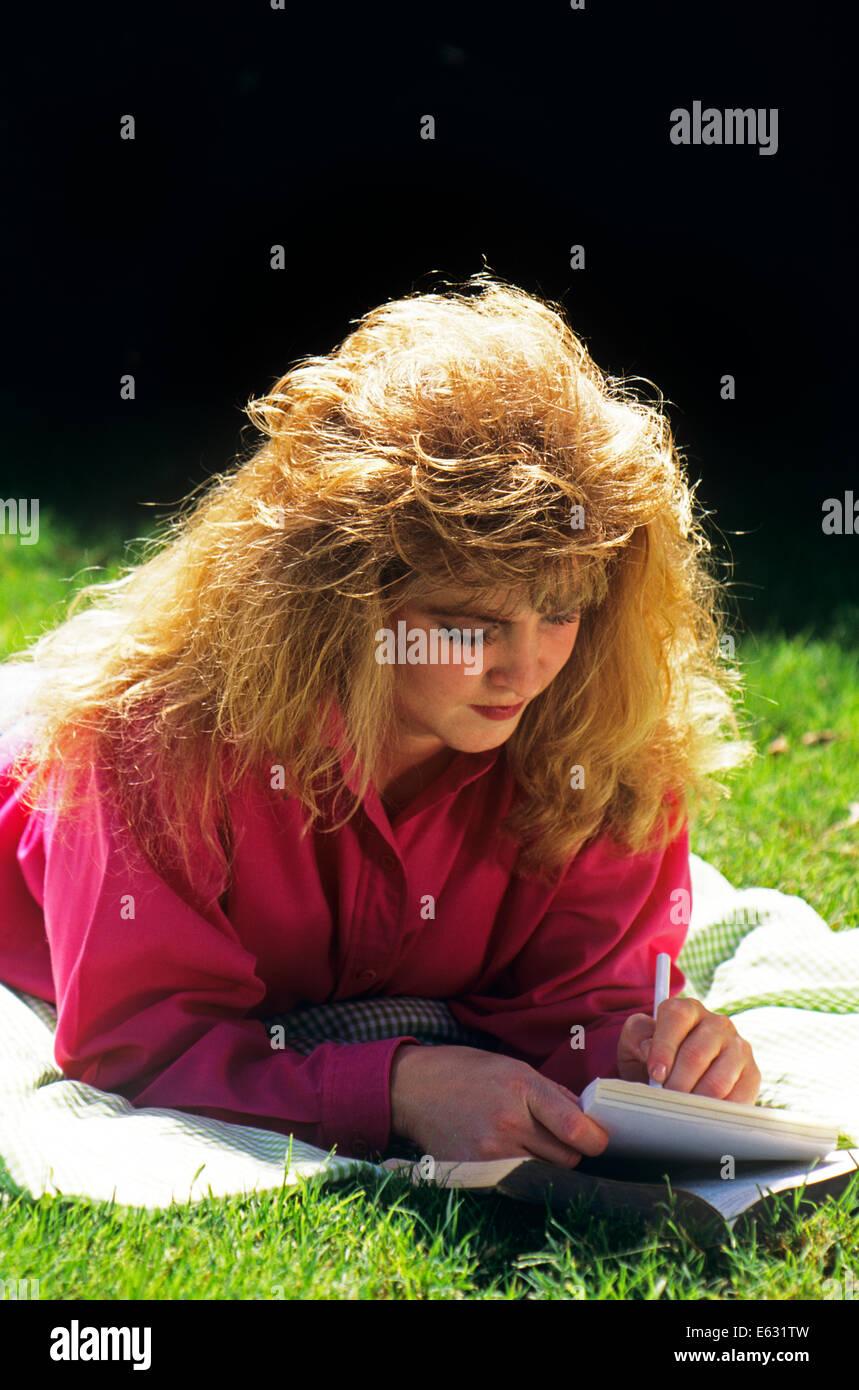 1980s TEEN GIRL OUTDOORS STUDYING WRITING Stock Photo