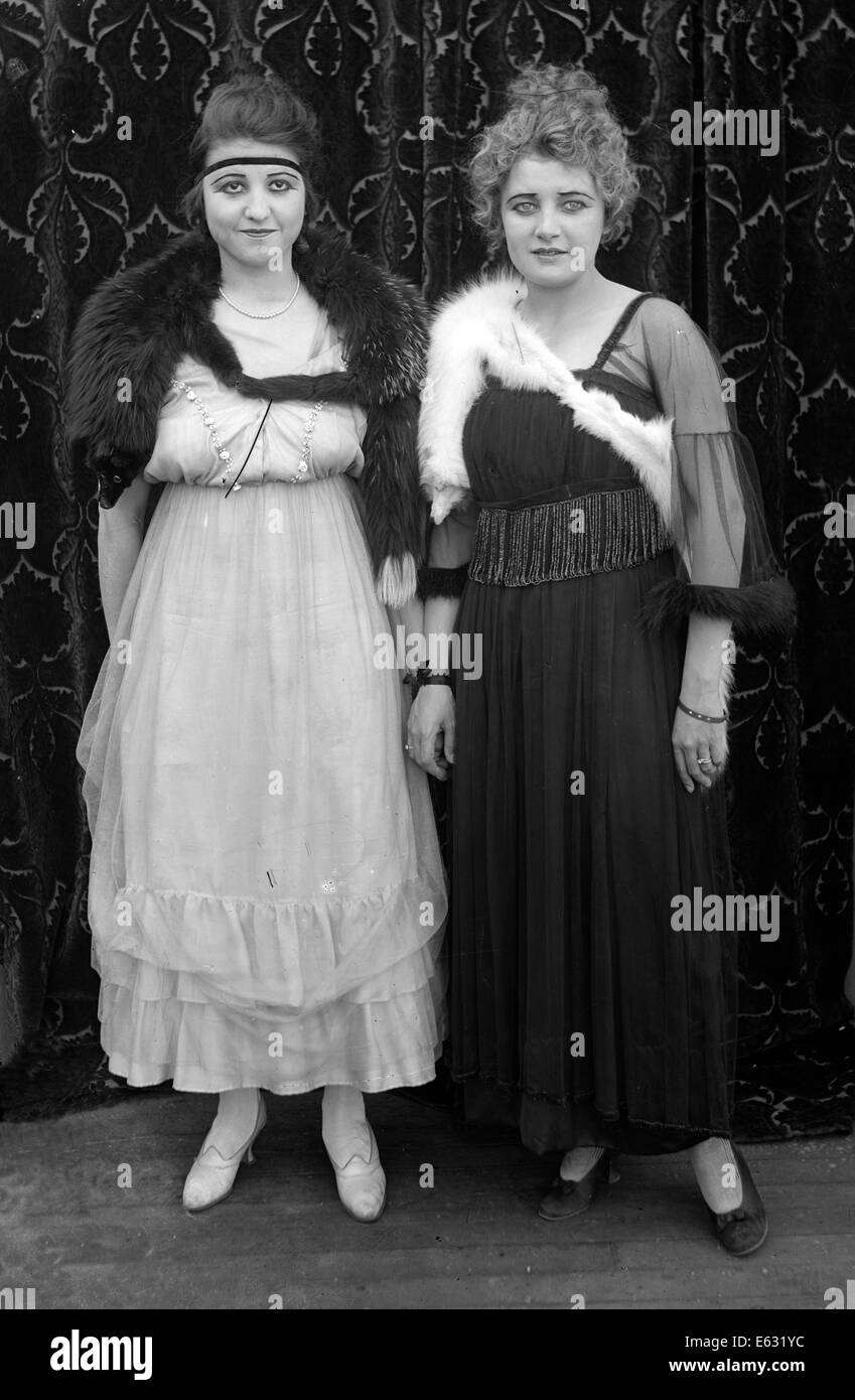 1900s 1910s TWO WOMEN STANDING SIDE BY SIDE WEARING STYLISH DRESSES LOOKING AT CAMERA SILENT MOVIE STILL - Stock Image