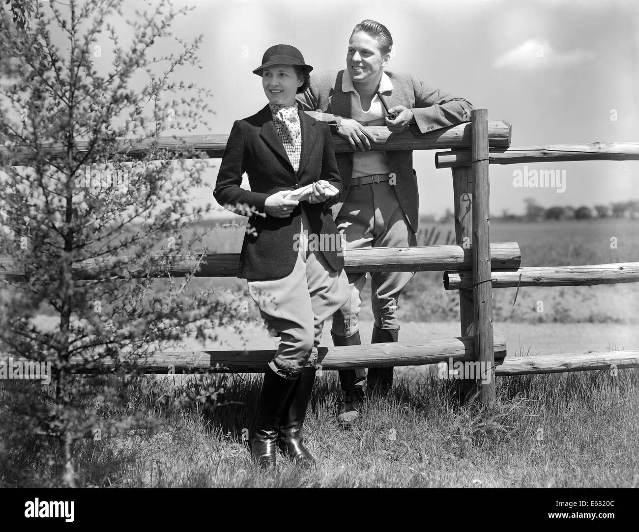 1930s COUPLE WEARING RIDING CLOTHES JODHPURS STANDING TOGETHER BY RAIL FENCE MAN SMOKING PIPE - Stock Image