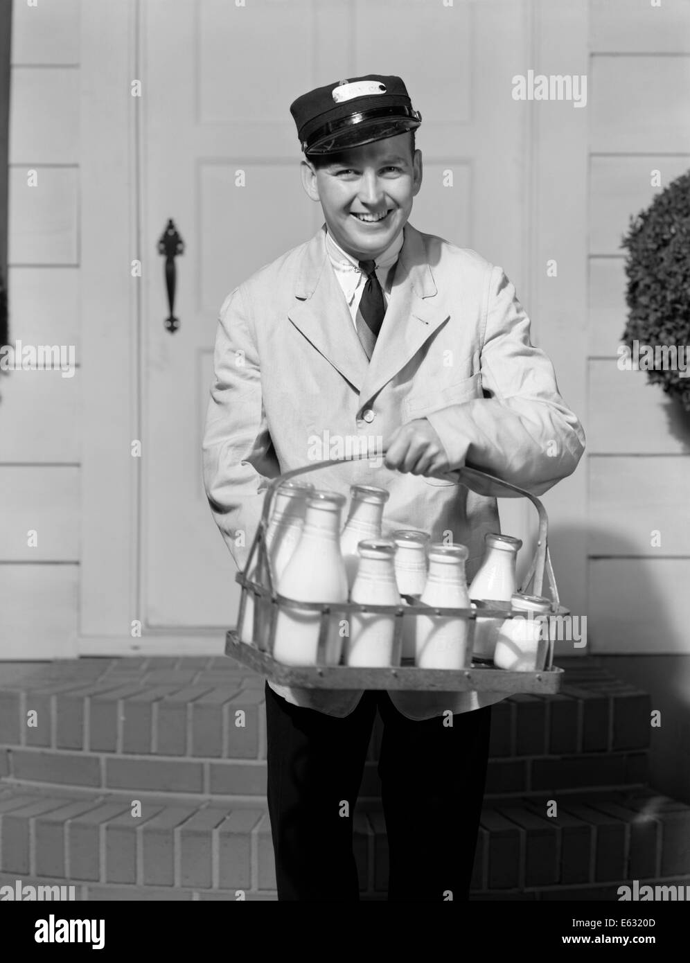 1930s Smiling Milkman Looking At Camera Delivering Milk In