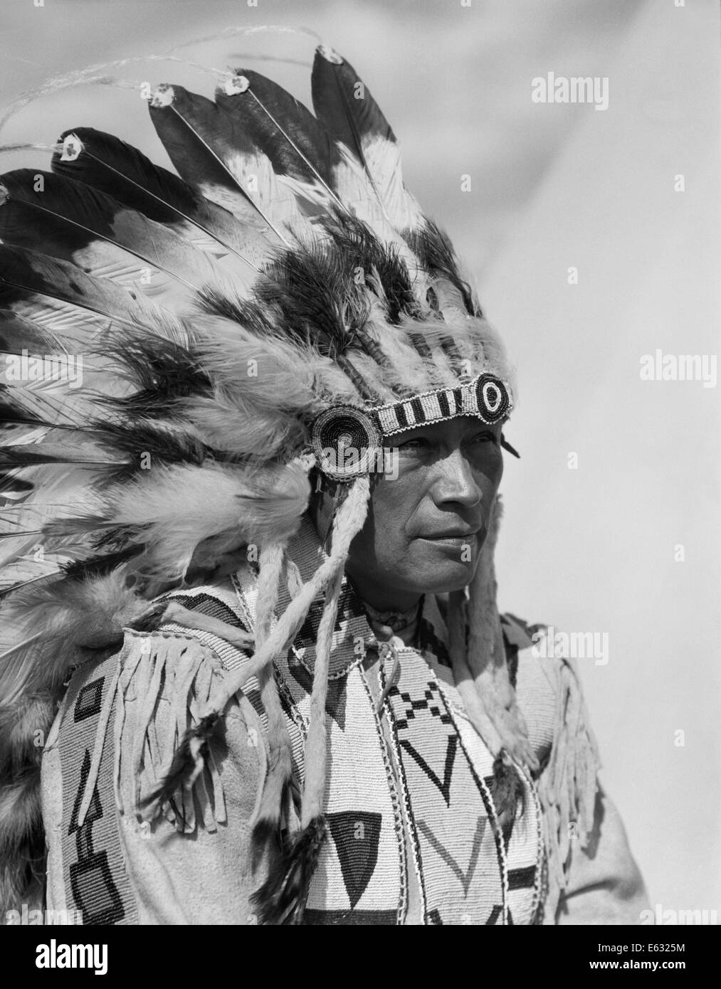 1920s PORTRAIT NATIVE AMERICAN MAN WEARING FULL FEATHER HEADDRESS STONEY SIOUX ALBERTA CANADA - Stock Image