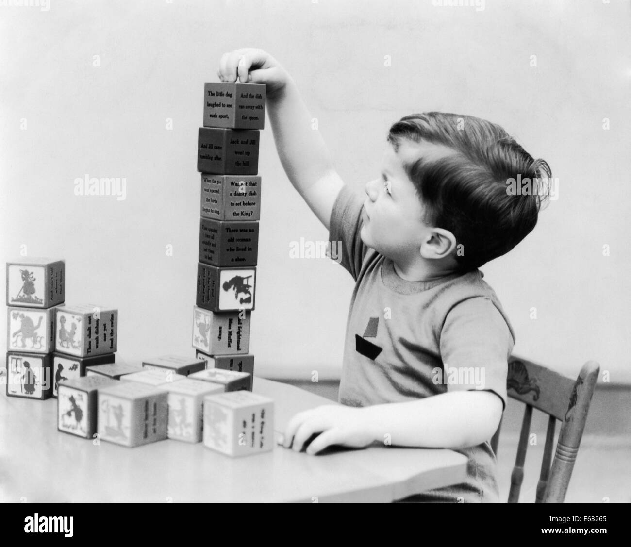 1930s BOY STACKING PLAYING WITH NURSERY RHYME THEME BUILDING BLOCKS TOYS - Stock Image