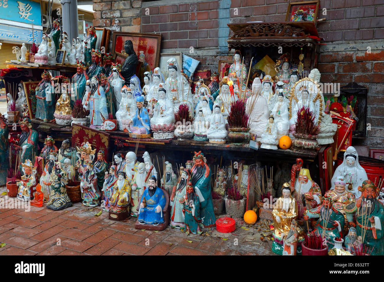 Adoration figures with incense on a small altar in the street, Kowloon, Hong Kong, China - Stock Image