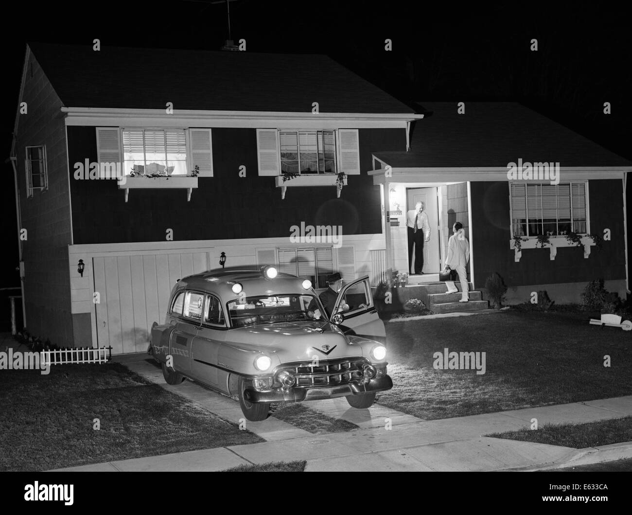 1950s AMBULANCE AT NIGHT PARKED IN SUBURBAN HOME DRIVEWAY WITH DOOR OPEN WHILE EMT DRIVER TALKS TO RESIDENT AT HOUSE - Stock Image