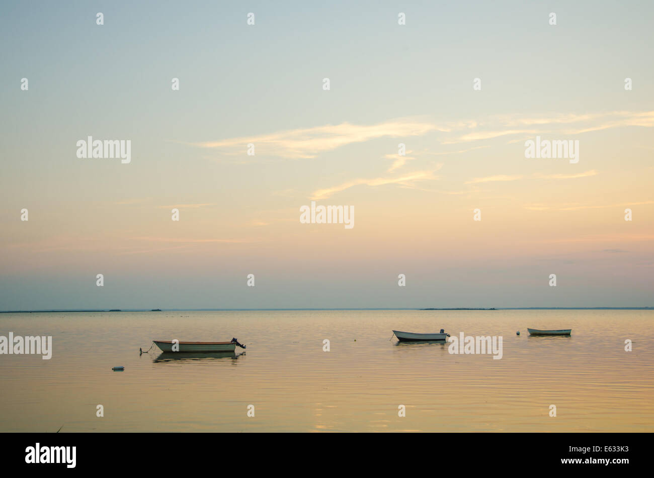 Anchored rowing boats at twilight in a calm bay - Stock Image