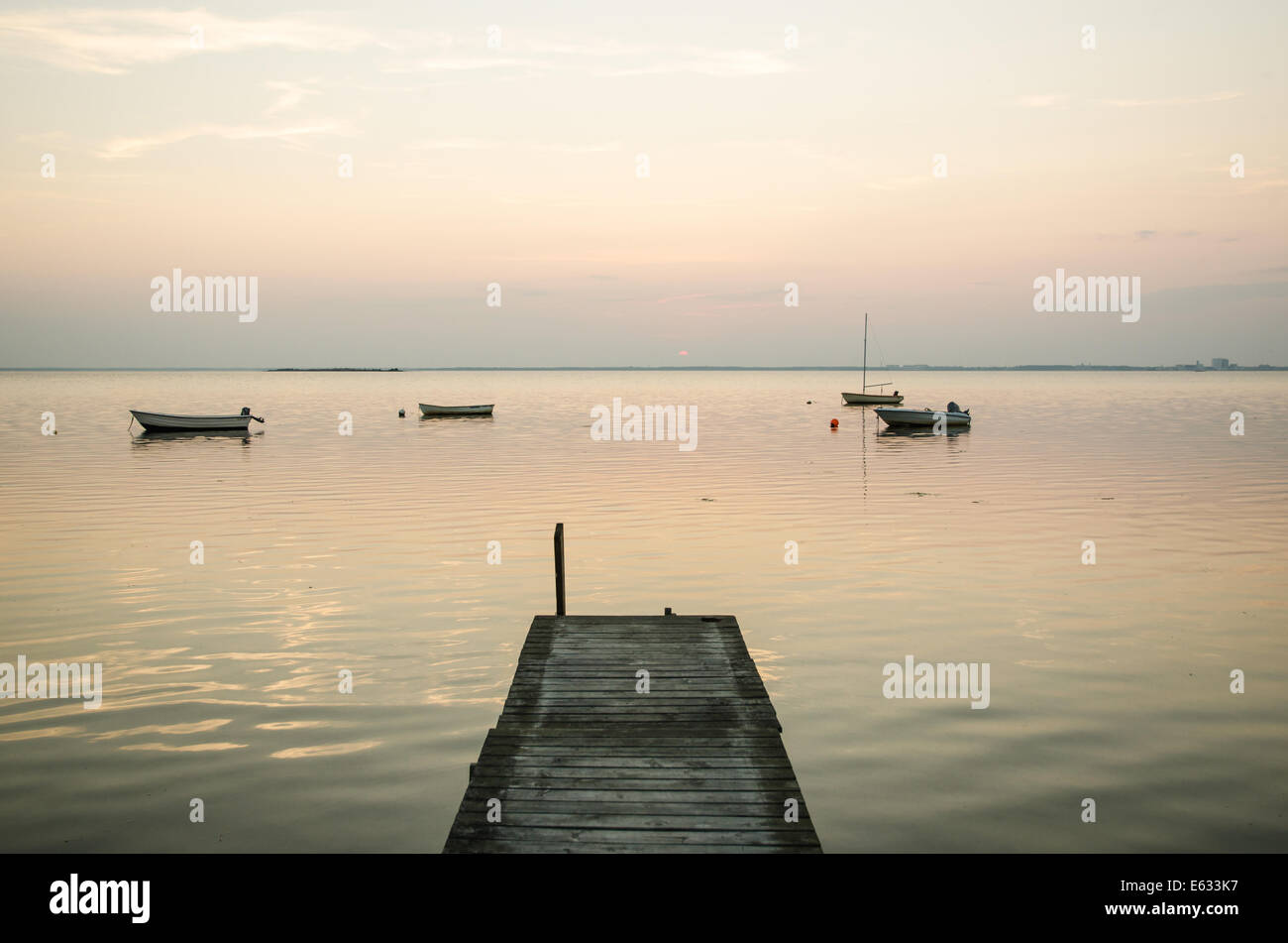 Old wooden jetty with anchored rowing boats at evening in a calm bay - Stock Image