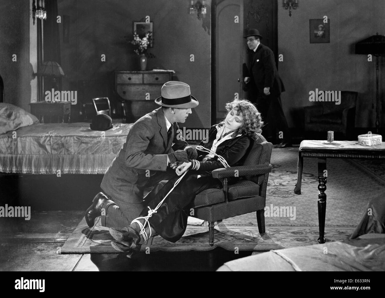 1930s MOVIE STILL OF MAN RESCUING WOMAN TIED UP IN CHAIR - Stock Image