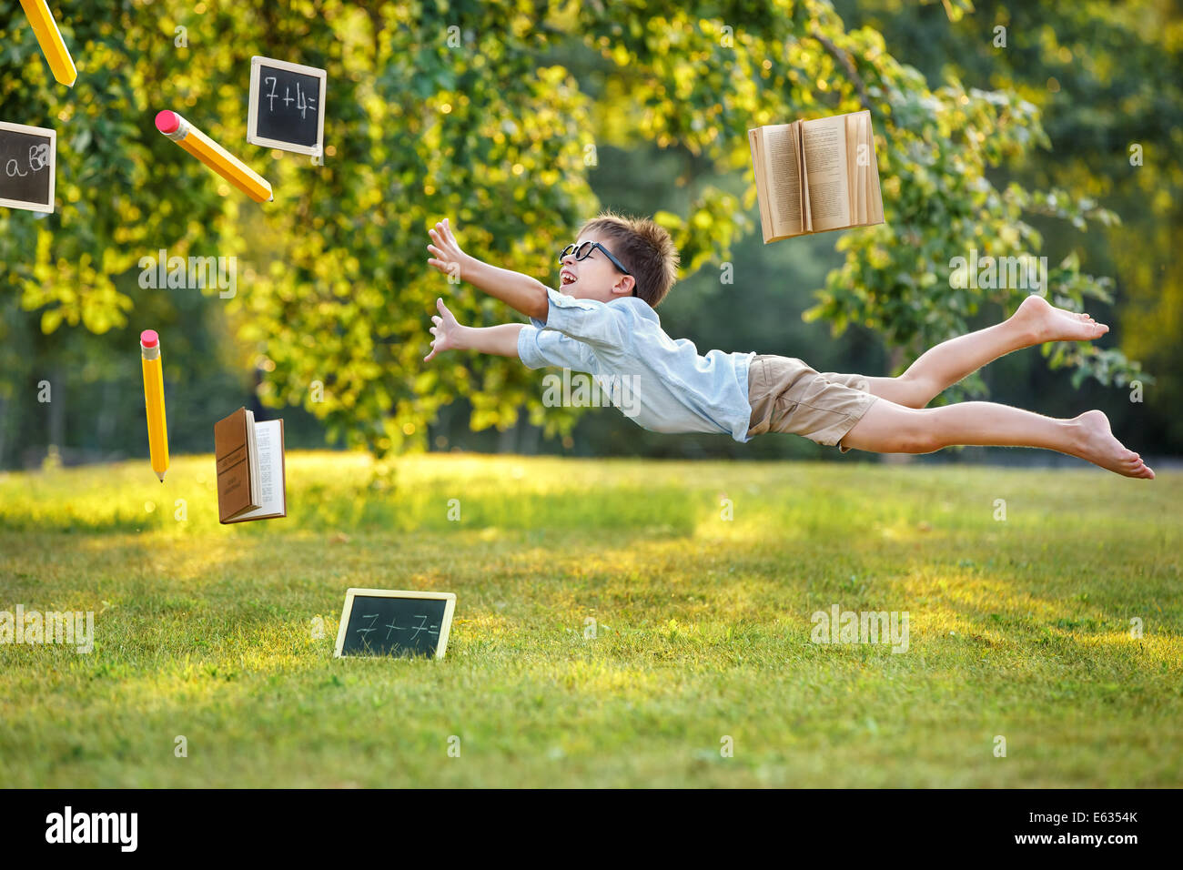 Thirst for knowledge, flying cute little boy - Stock Image